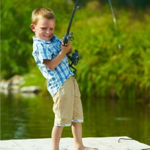 Young boy catching a fish on a dock